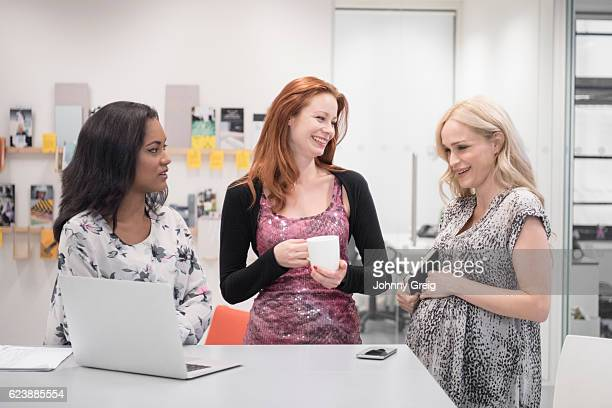Three businesswoman smiling in office, pregnant woman holding notebook