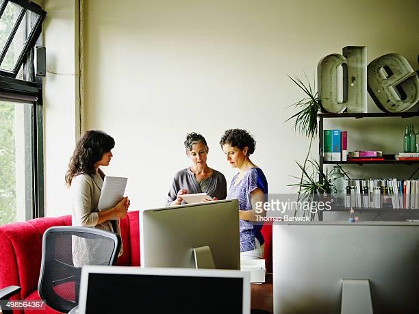 Three businesswoman working on digital tablet