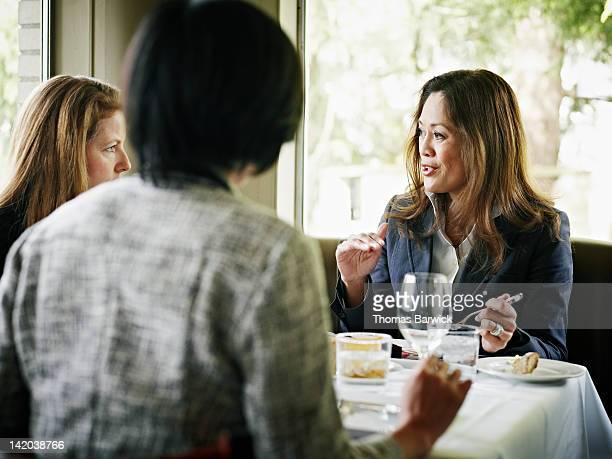 Three businesswomen at table in restaurant