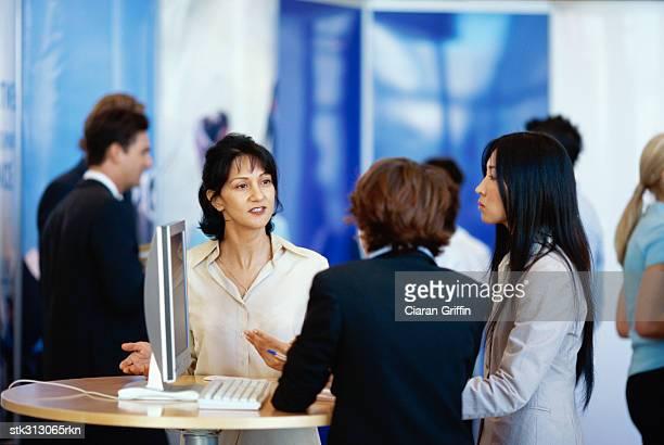 three businesswomen discussing at an exhibition