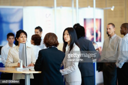 three businesswomen discussing at an exhibition