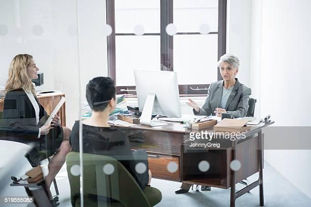 Trois femmes d'affaires en réunion de cloison en verre
