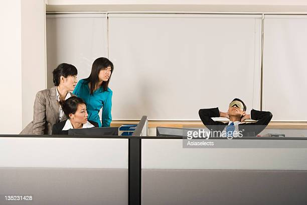 Three businesswomen looking at a businessman sleeping on a chair in an office cubicle