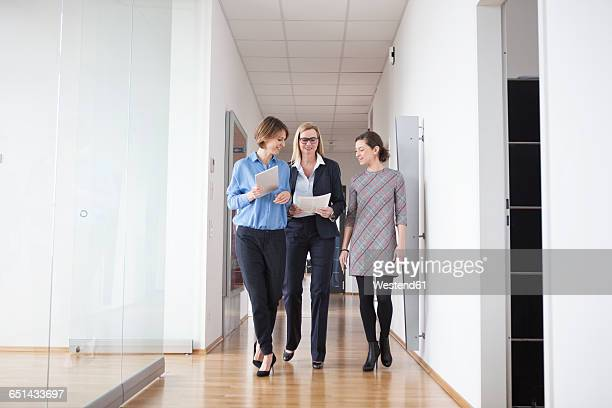 Three businesswomen walking and talking in office hall