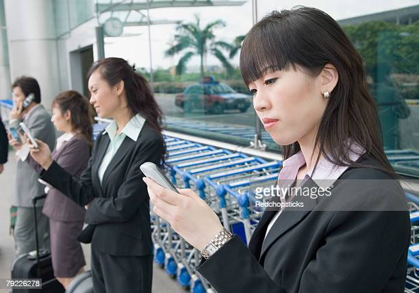 Three businesswomen with a businessman waiting at an airport lounge