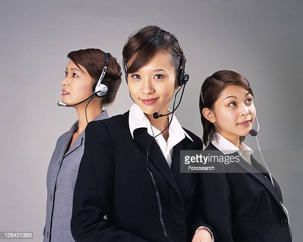Three Businesswomen with headsets smiling, Studio, Portrait