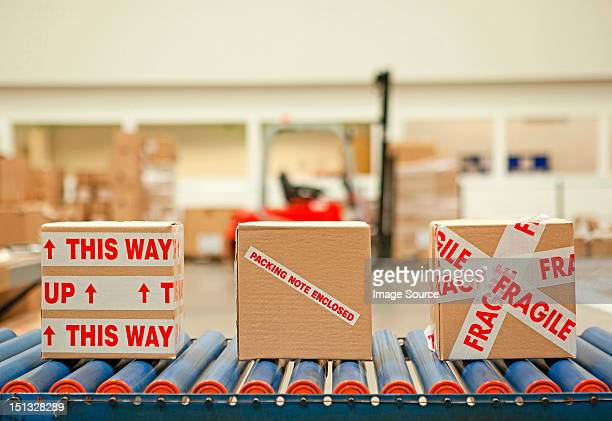 Three cardboard boxes with parcel tape on conveyor belt
