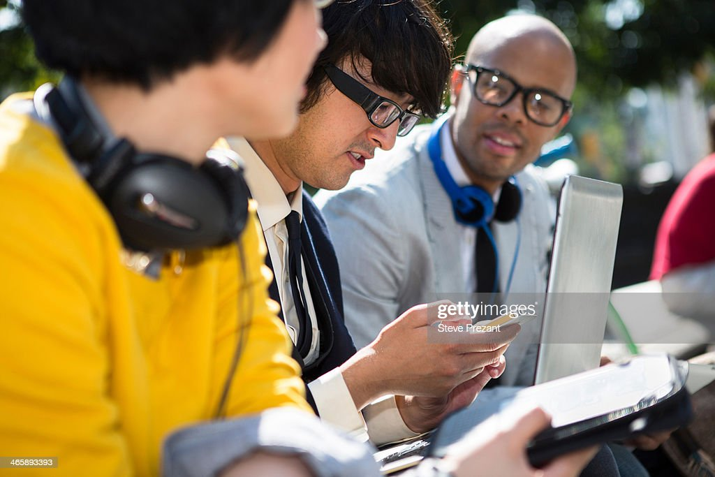 Three casual businesspeople using laptop in park