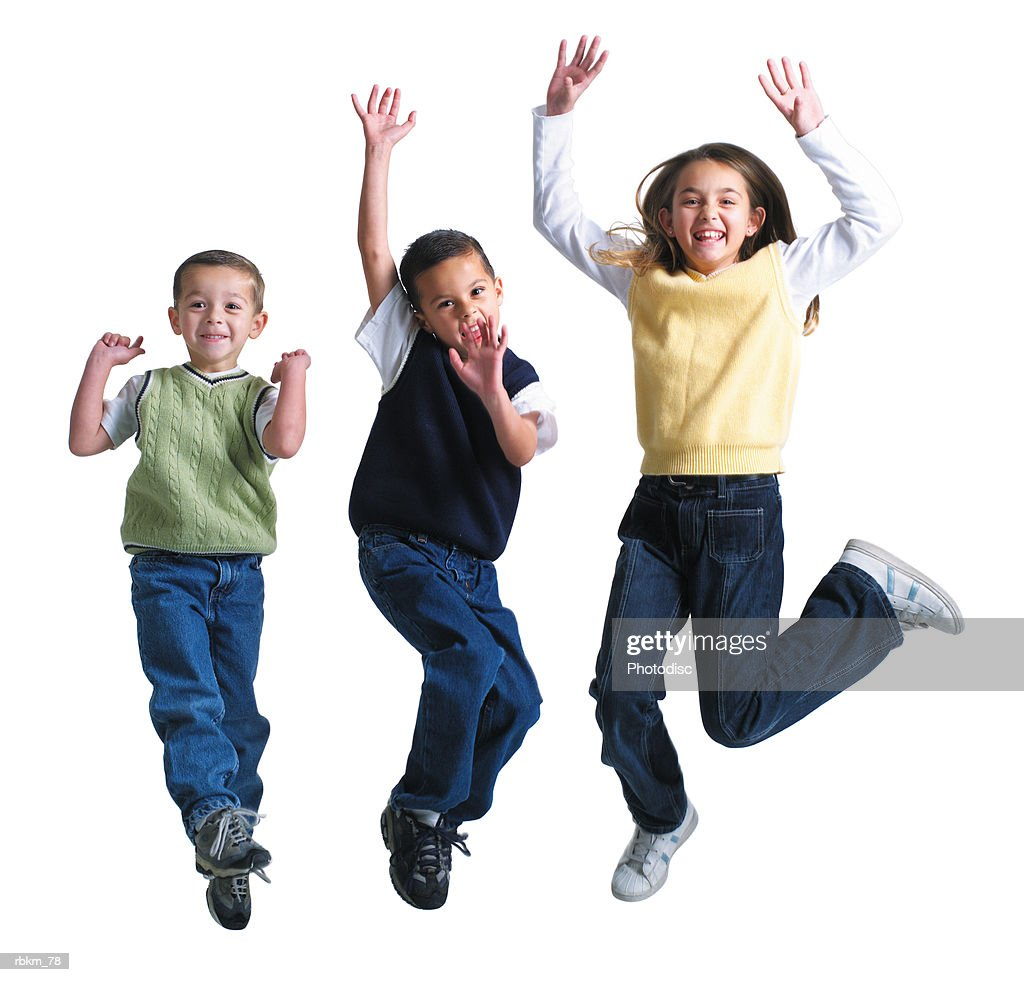 three caucasian siblings jump up into the air and laugh while playing together : Stock Photo