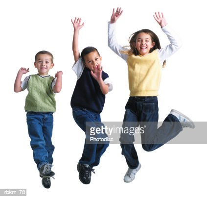 three caucasian siblings jump up into the air and laugh while playing together : Stockfoto