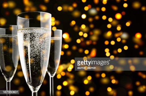 Three Champagne glasses with sparklings, yellow lights in the background