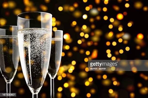 Drei Champagner-Gläser mit sparklings, gelben Lichtern im Hintergrund