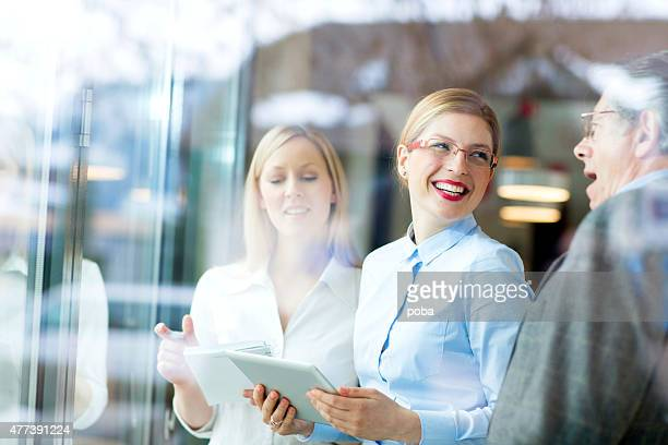 Three cheerful  businesspeople looking on a touchpad