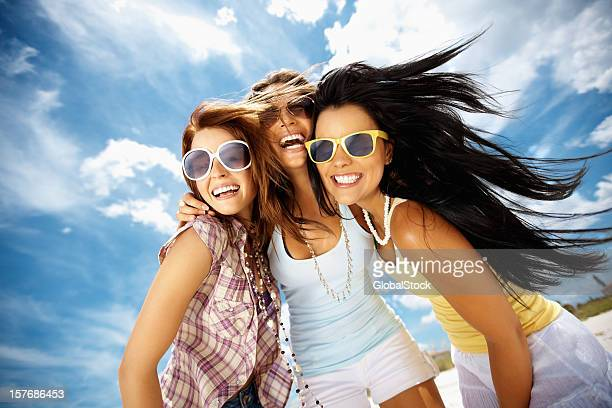 Three cheerful young friends wearing sunglasses against sky