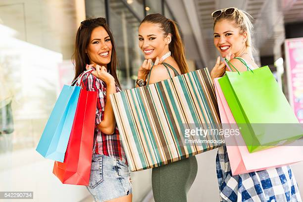 Drei fröhliche junge Frauen Spaß haben Einkaufsmöglichkeiten, Lachen, Bindung.