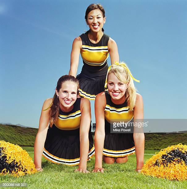 Three cheerleaders forming human pyramid on field, portrait