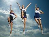Three cheerleaders jumping