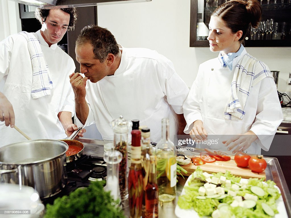 Three chefs in kitchen, one tasting sause on finger : Stock Photo
