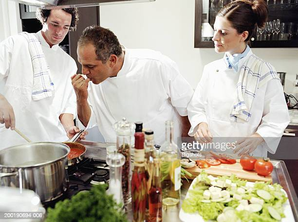 Three chefs in kitchen, one tasting sause on finger