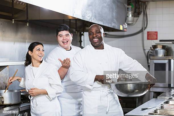 Three chefs working in a commercial kitchen