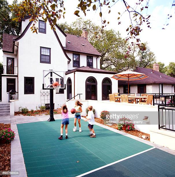 Three children are seen playing the basketball game
