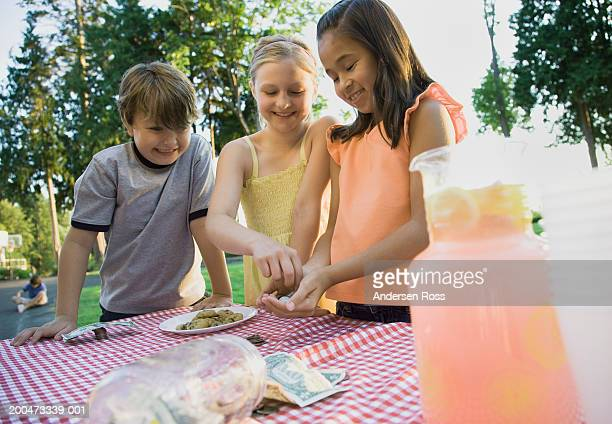 Three children (7-10) beside lemonade stand, smiling
