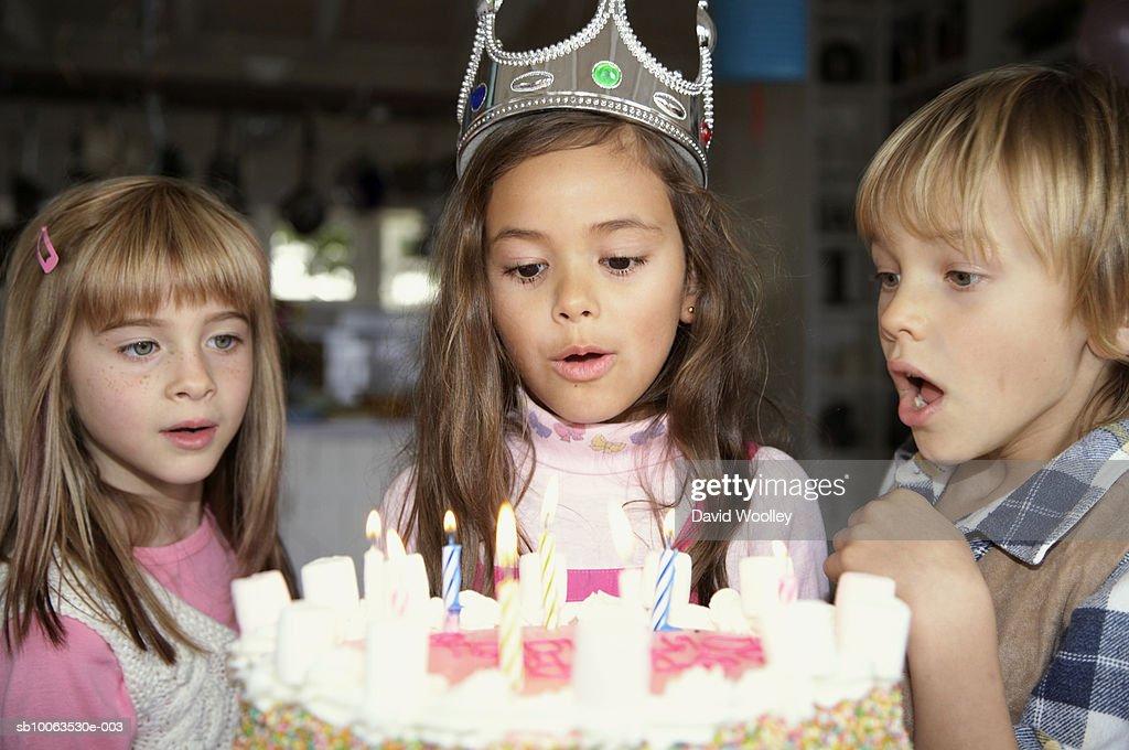 Three children (4-7) blowing candles on birthday cake : Stock Photo