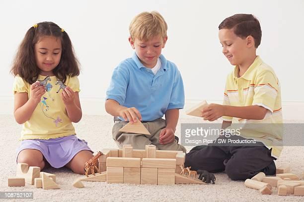 Three Children Building Noah's Ark With Wooden Blocks