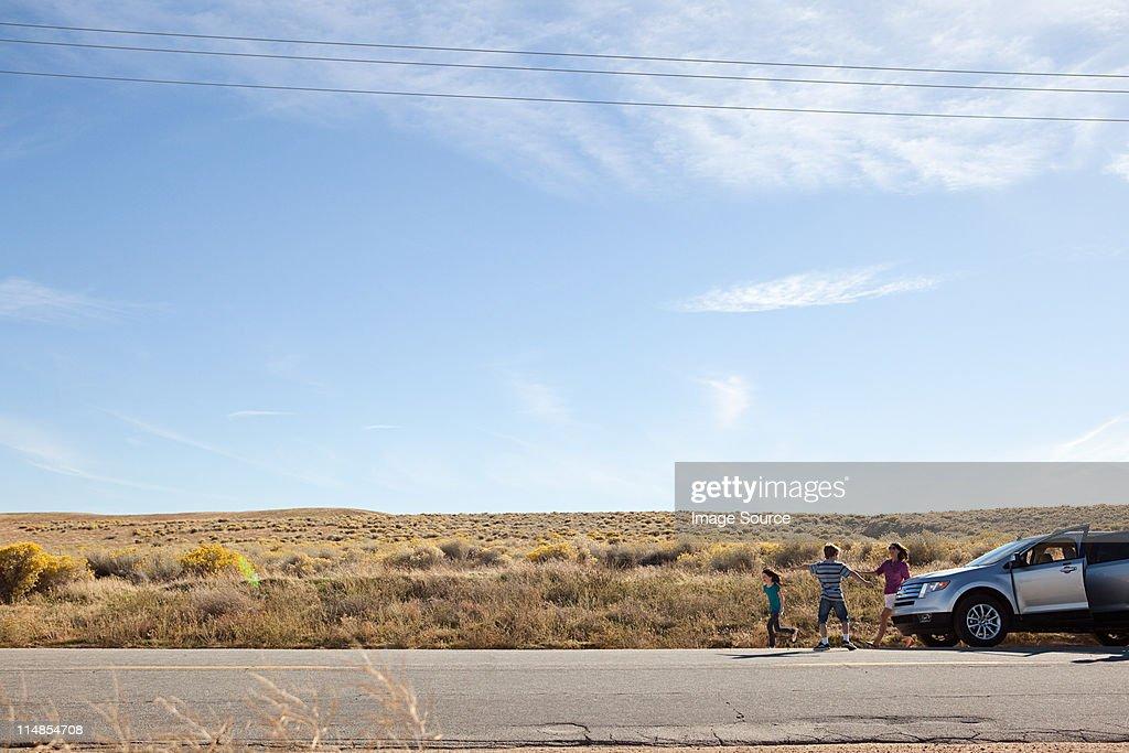 Three children by parked car in desert