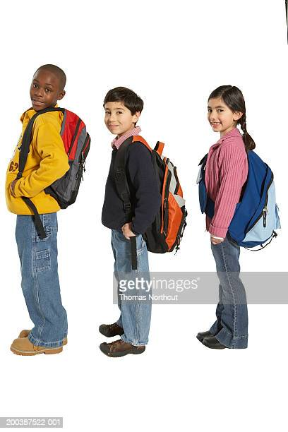 Three children (7-9) carrying backpacks and shoulder bag, side view