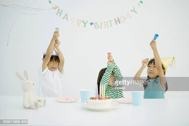 Three children (3-6) celebrating birthday, releasing party poppers