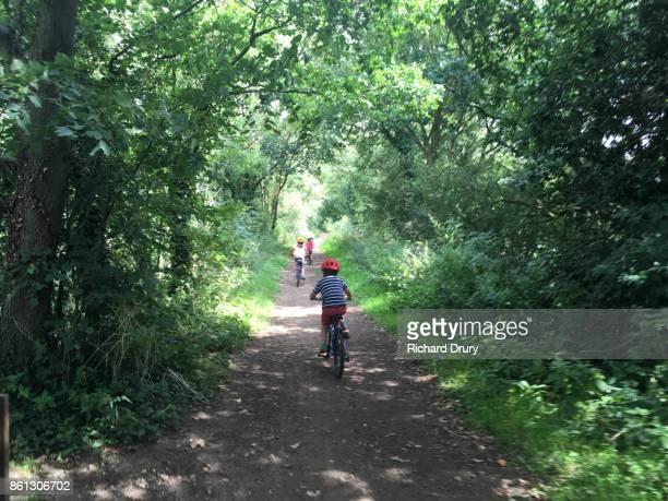 Three children cycling on a trail