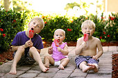 Three young children, including two brothers and a baby sister are sitting outside in the garden, eating strawberry fruit popsicles on a summer day.