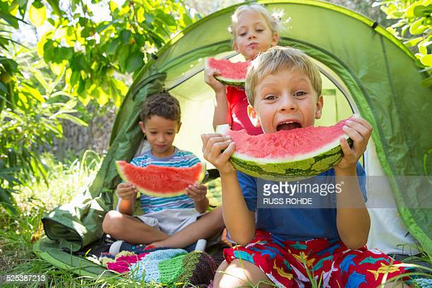 Three children eating large watermelon slices in garden tent