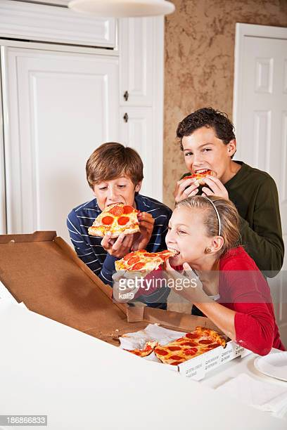 Three children eating pizza from take out box