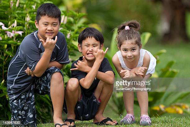 Three children give hang loose hand sign
