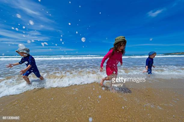 Three Children having fun Running away from the Ocean Waves.