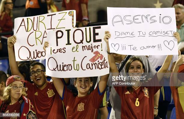 Three children hold up placards cheering spain's forward Aritz Aduriz Spain's midfielder Marco Asensio and Spain's defender Gerard Pique during the...