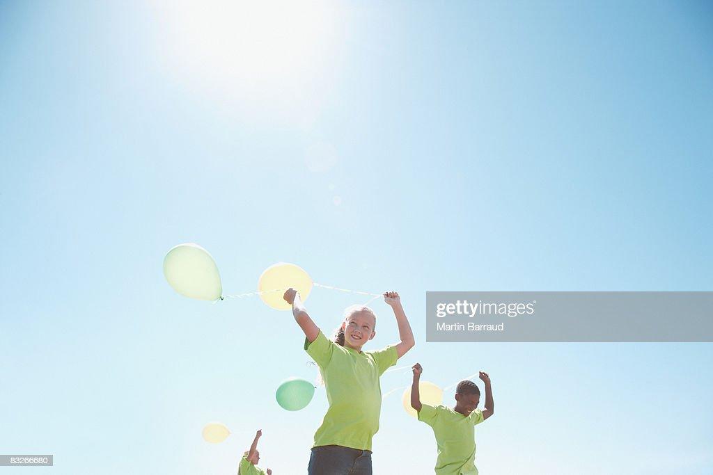 Three children holding balloons outdoors : Stock Photo