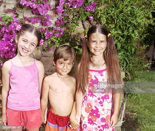 Three children (5-8) holding hands outdoors, portrait