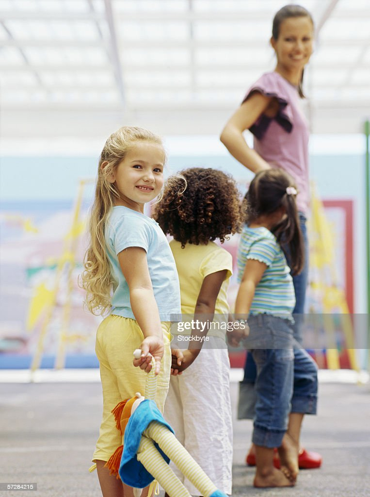Three children holding hands with a teacher : Stock Photo