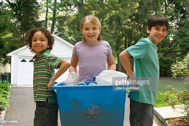 Three children holding up recycle container