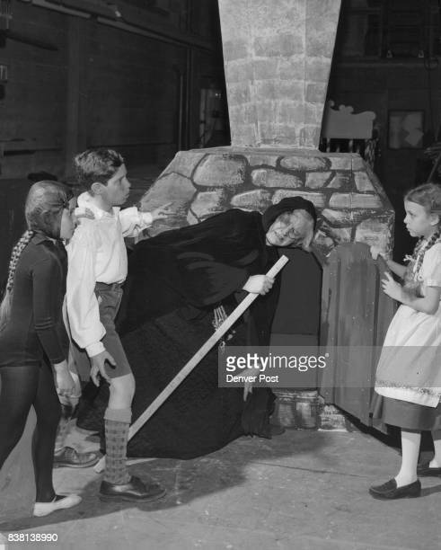 Three children imprisoned by the evil witch in Madge Miller's adaptation of 'Hansel and Gretel' line up the sorceress for a quick push into the oven...