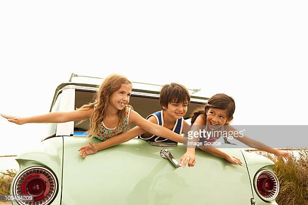 Three children in back of estate car with arms out
