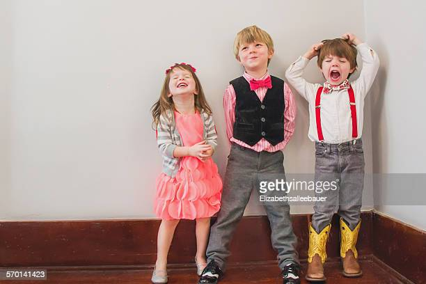 Three children in fancy dress messing about