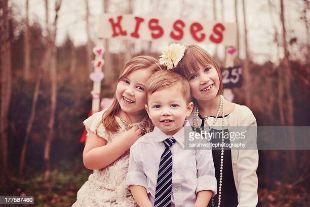 three children in front of a kissing booth