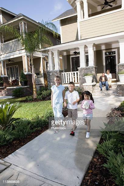 Three children in front of their house while their parents watch from front steps