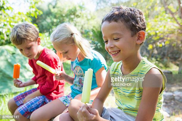 Three children in garden eating ice lollies