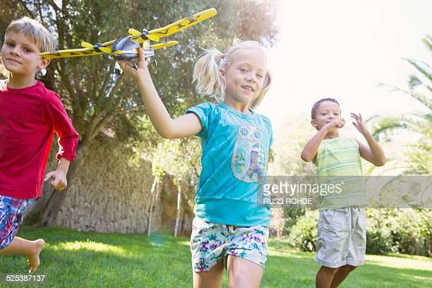 Three children in garden running with toy airplane