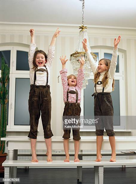 Three children in lederhosen cheering